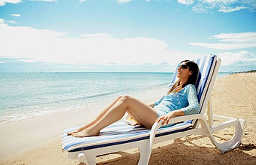 Woman on the couch by the beach : Stock Photo