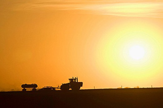 Stock Photo: 1566-442388 Large modern tractor pulls disc and anhydrous ammonia tank as he discs in fertilizer in the spring near Iowa Falls, Iowa, USA  Photo is set against large setting sun