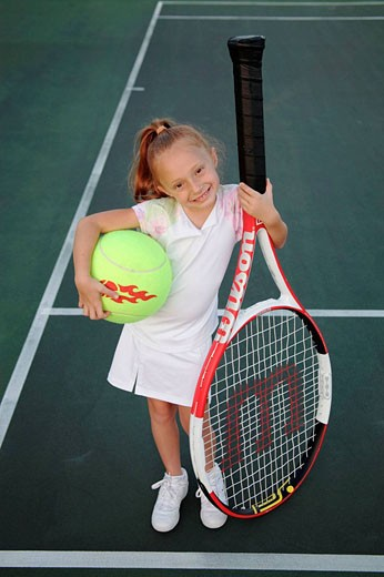 Kid with an oversized tennis racket and ball : Stock Photo