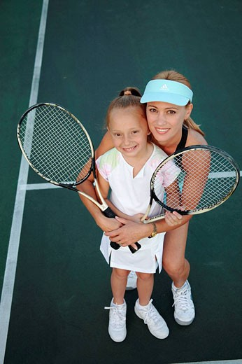 Stock Photo: 1566-446186 Mother and daughter posing with tennis rackets