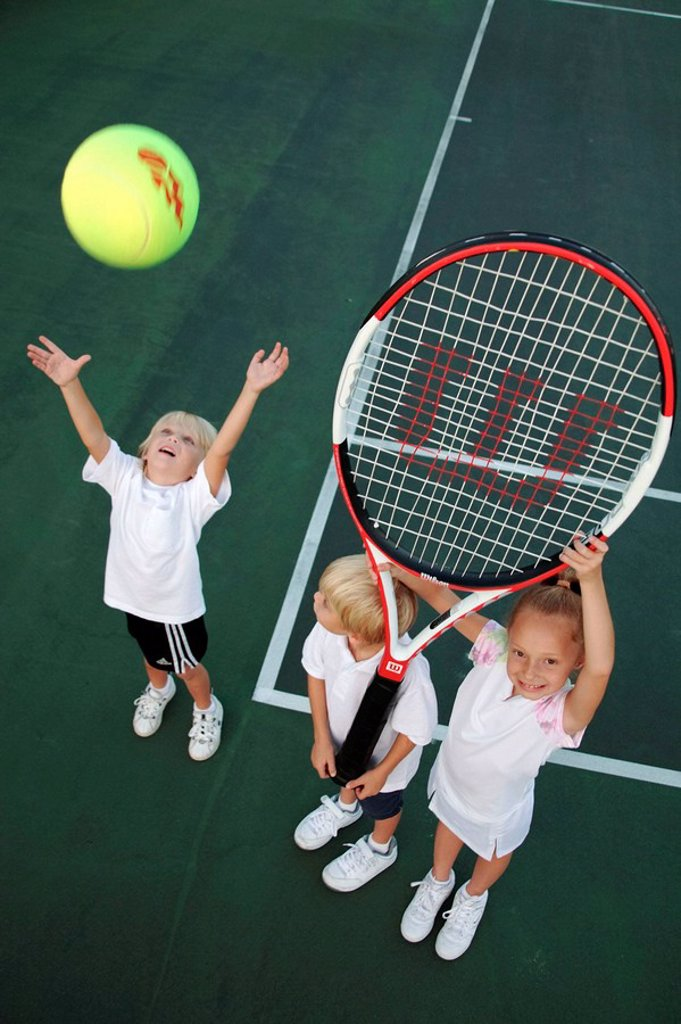 Kids playing with an oversized tennis racket and ball : Stock Photo