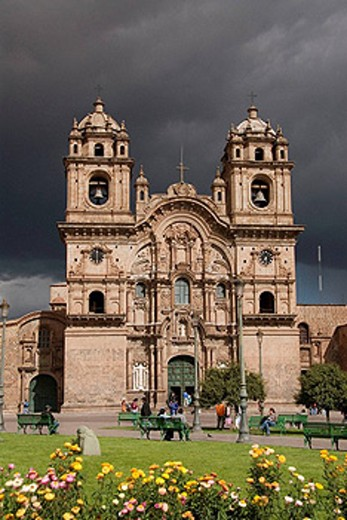Peru, Cuzco, Plaza de Armas, Church of La Compania de Jesus, originally built by the Jesuits in 1571, immediately re-built after the earthquake of 1650, has a beautiful baroque facade,  a brewing rain storm in background, flowers in the foreground : Stock Photo
