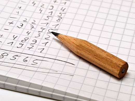 checked memo pad with a long sequence of numbers, beside is a small pencil : Stock Photo