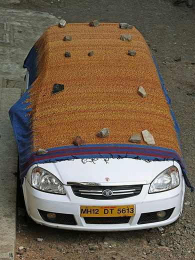A car is covered with a big cloth  Pune, Maharashtra, India : Stock Photo