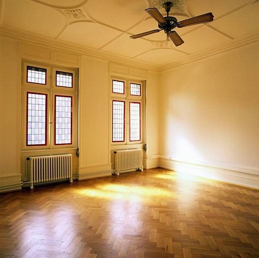 Stock Photo: 1566-452579 Sunny empty room with oak wooden flooring and two stained glass windows and ceiling fan