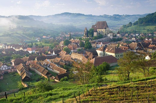 Biertan village with fortified church in morning mist. Romania : Stock Photo