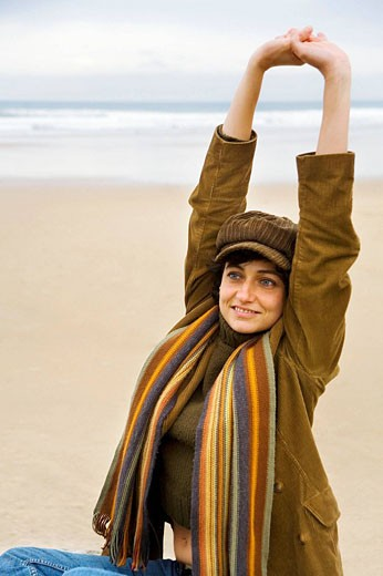 Portrait of a young woman with cap and scarf stretching out in a beach and smiling : Stock Photo