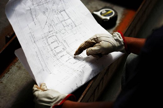 Construction worker pointing to architectural plan : Stock Photo