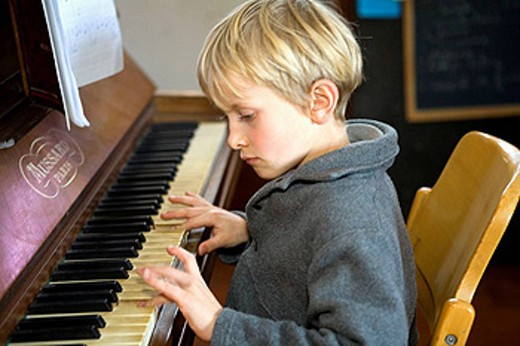 Stock Photo: 1566-460410 Young boy practicing the piano