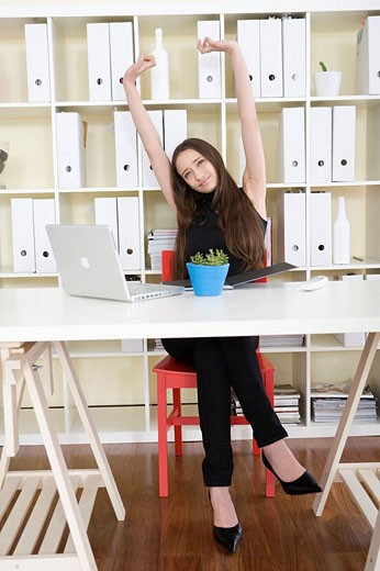 Stock Photo: 1566-464131 Businesswoman stretching at desk