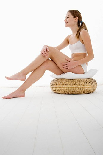 Stock Photo: 1566-464454 young woman applying moisturizer on her leg