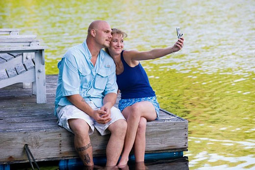 Stock Photo: 1566-471035 couple on dock taking photo with camera phone