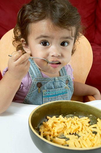 Little girl eating macaroni and cheese. : Stock Photo