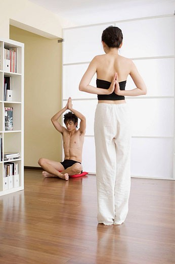 Young couple in yoga attitude, indoors : Stock Photo