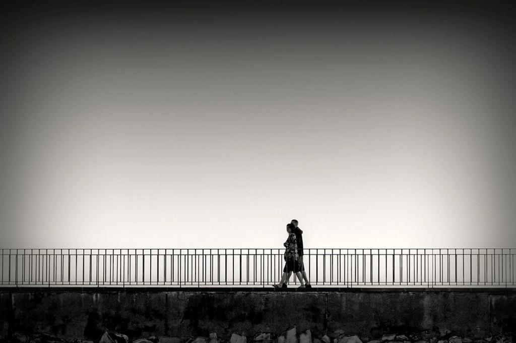 Pareja de jóvenes paseando por un puente al atardecer. Blanco y Negro. Puerto de Cambrils; Costa Dorada; Tarragona; Spain. : Stock Photo