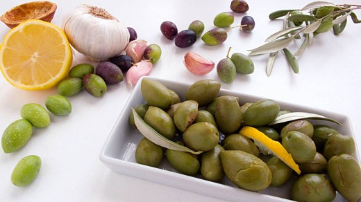 Seasoned olives, lemon, garlic and herbs : Stock Photo