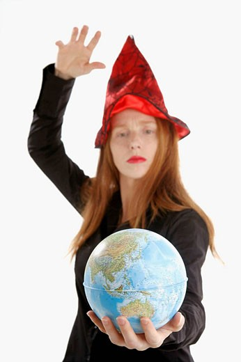 Beautifull witch incantanting a global map : Stock Photo