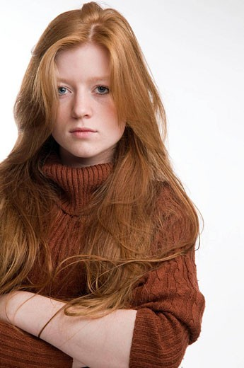 Stock Photo: 1566-475913 Red haired teenage girl looking moody, arms crossed, staring at the camera. portrait