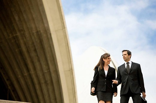 MR business man and woman (ages 43 and 42) walking near Opera House.   Sydney, Australia : Stock Photo