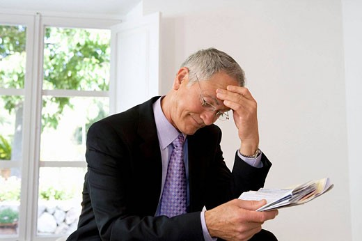 Businessman looking at papers : Stock Photo