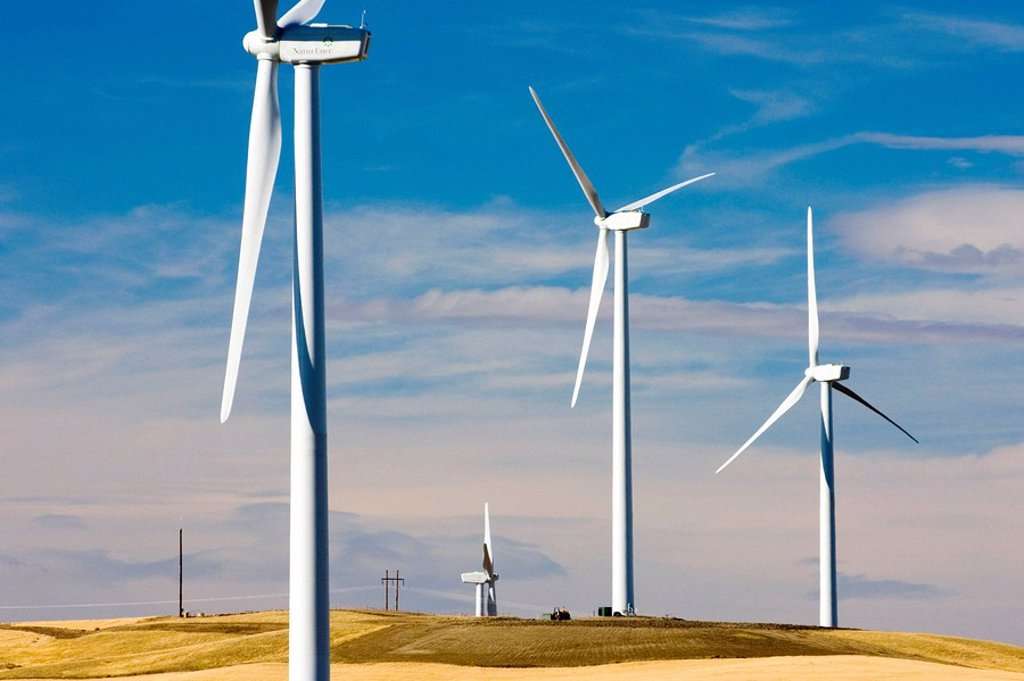 Stock Photo: 1566-482900 Wind turbines stand amidst the plains of eastern Montana near the Rocky Mountain front ranges of Glacier National Park USA