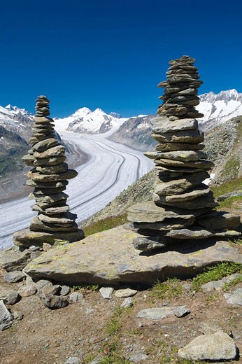 Piled stones to mark the road in the mountains  Valley glacier with its longitudinal moraines of the Glacier Alesht  At the bottom the summits of the Monch, the Junfrau and the Eiger  Berneses Alps  Switzerland : Stock Photo