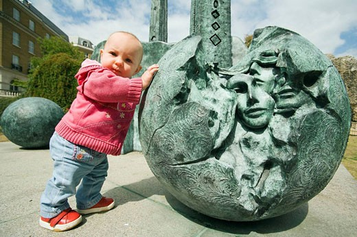Stock Photo: 1566-485428 Baby girl pushing a ball of the contemporary sculpture near Reading Abbey Berkshire, England