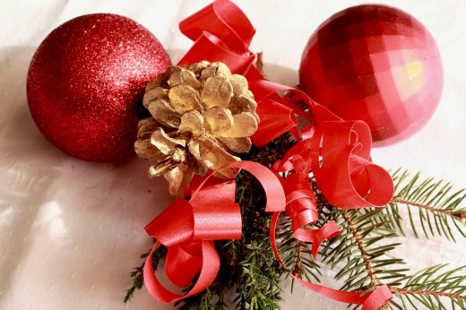 Stock Photo: 1566-485434 Two red Christmas balls with red ribbon and yew on white linen Two red Christmas balls with red ribbon and yew on white linen Two crimson balls with a gilt pine cone with yew are on white damask linen