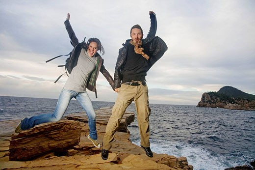 Couple jumping in a cliff by the sea : Stock Photo