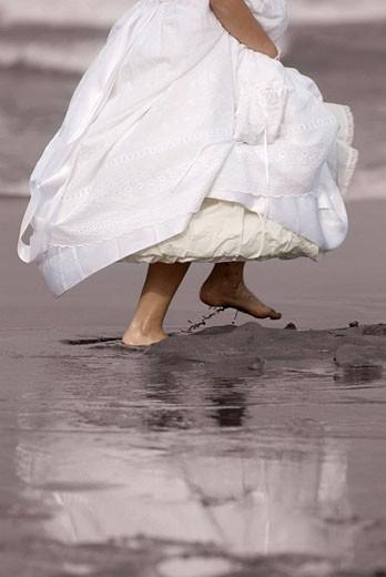 Stock Photo: 1566-487814 niña vestida con traje de comunion corriendo por la orilla de la playa