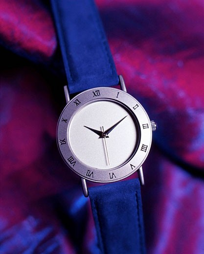 Stock Photo: 1566-487882 Watch with roman numeral on a purple silken background