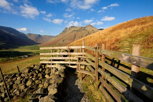 Footpath and stile with Great Langdale and the Langdale Pikes beyond, Lake District, Cumbria, England : Stock Photo