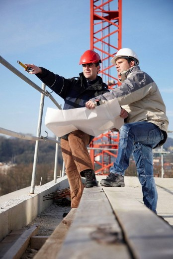 Architect and construction worker looking at blueprints, personal protective equipment, housing construction : Stock Photo