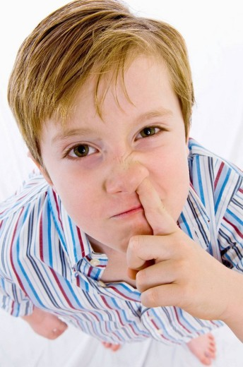 a child who puts his fingers in the nose : Stock Photo