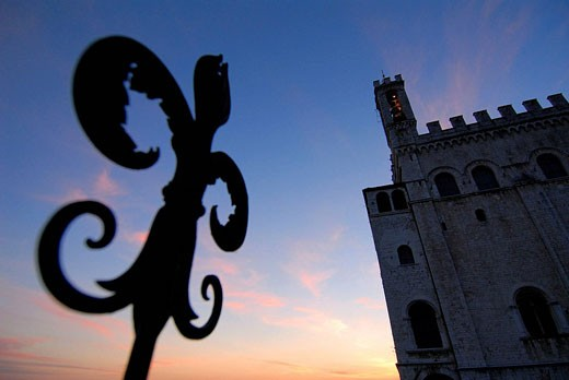 Gubbio Umbria Italy Palazzo dei Consoli and the wrought iron Fleur de Lys, a motif found throughout the town : Stock Photo
