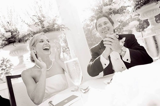 bride and groom laughing at reception : Stock Photo