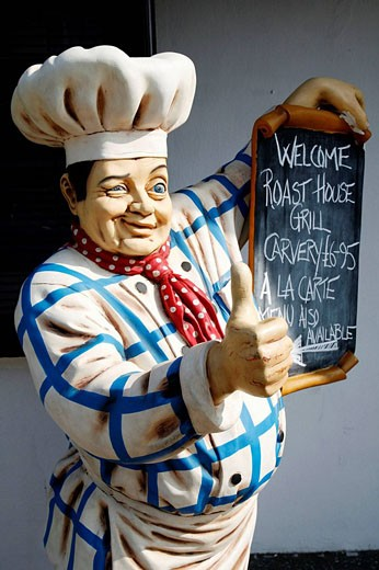 Giant model male chef with traditional chef´s hat and clothing winking and showing thumbs up holding menu : Stock Photo
