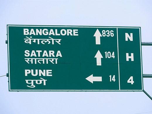 Stock Photo: 1566-499806 A signboard on a national highway four roadside is showing distances of Bangalore, Karad, Satara from Pune  Maharashtra, India