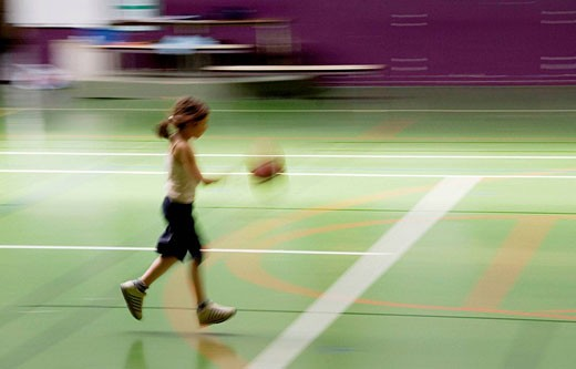 child playing basketball, in a scholl gymnase : Stock Photo