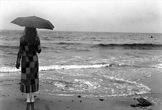 Mujer joven con paraguas en la orilla del mar   Young Woman Standing Under Cloudy Sky : Stock Photo