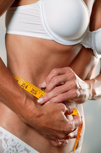 A healthy woman measures her waist : Stock Photo
