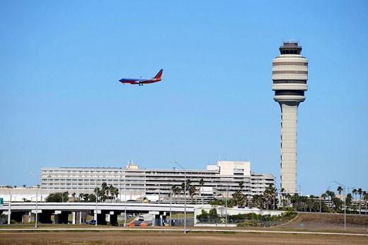 Airplane Jet prepares to land Control Tower at Orlando International Airport Florida : Stock Photo