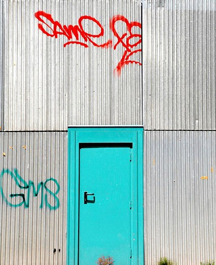 painted door and aluminum sided factory building : Stock Photo