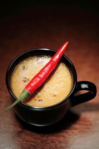 A cup of coffee with chili peper : Stock Photo