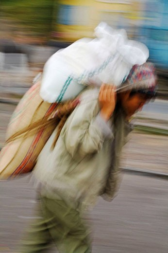 India, West Bengal, Darjeeling, Railway station, Porter carrying load on back : Stock Photo