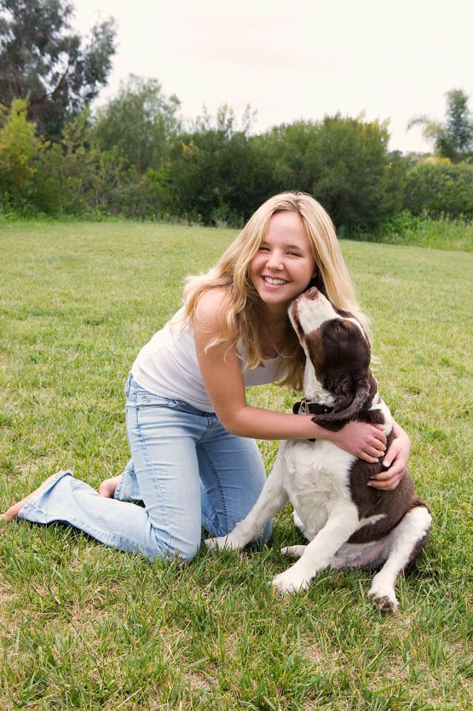 Smiling blonde teen girl in blue jeans and white tank top kneeling on grass lawn, get´s a kiss from her pet dog. : Stock Photo