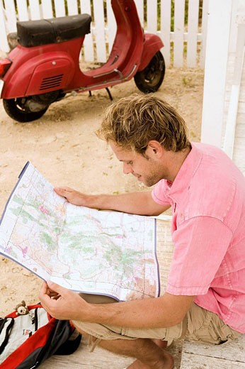 Man looking up in a map : Stock Photo