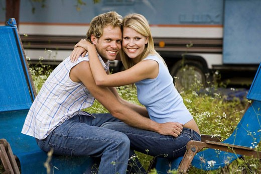 Stock Photo: 1566-521661 Young couple happy in front of a caravan