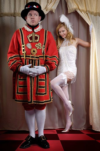 Yeomen of the Guard - Beefeater looking sideways at a beautiful young lady appearing from behind of a curtain : Stock Photo