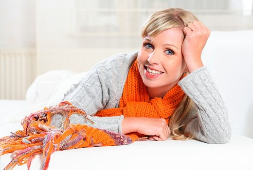 Stock Photo: 1566-523198 woman, person 20,25,30,30 +, years, femme,female blond, blond jacket, scarf, cardigan, blanket, blankets, covered, lies, lying, sofa, couch, bed, relaxation, relaxed, relax, relaxing , warm up, freeze, freeze, freezing, halsschmerzen ausstrahlung, positiv